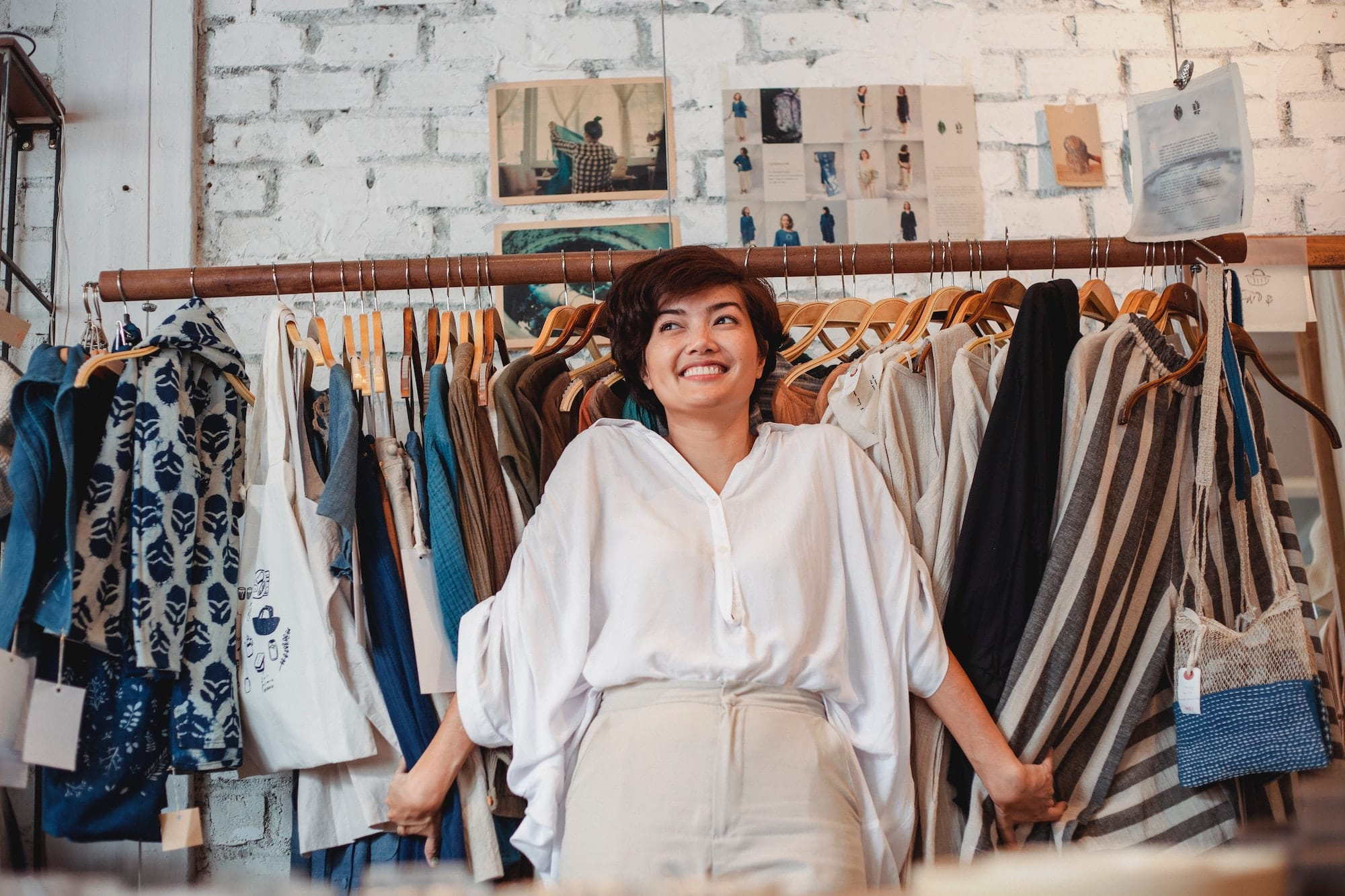Happy woman standing in front of clothes