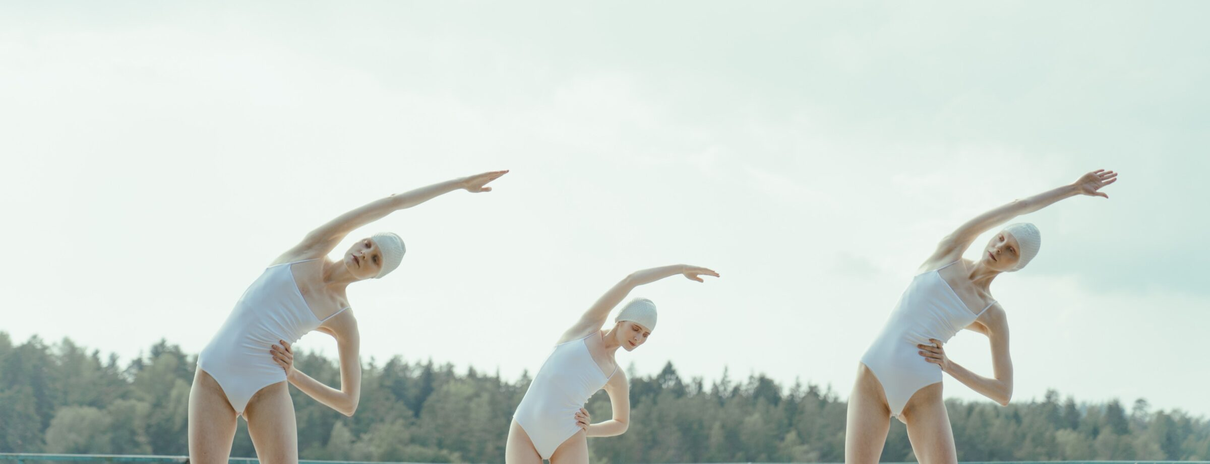 women wearing white swimsuits on a beach and stretching